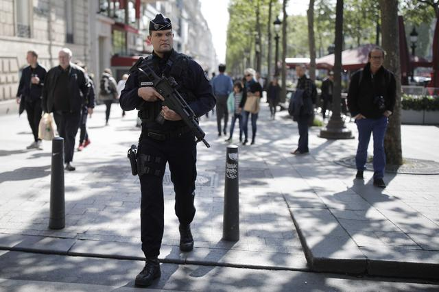 An armed French policeman patrols  the Champs Elysees Avenue the day after a policeman was killed and two others were wounded in a shooting incident in Paris, France, April 21, 2017. REUTERS/Benoit Tessier