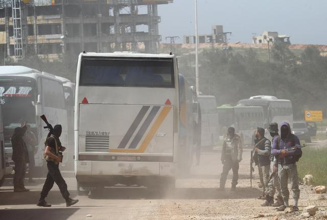 Rebel fighters stand guard as a convoy of buses (R) carrying Sunni rebels and civilians, who were evacuated from Zabadani and Madaya, as part of a reciprocal evacuation deal for four besieged towns, travel in al-Rashideen to journey towards rebel-held Idlib, Syria April 21 2017. REUTERS/Ammar Abdullah