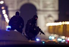 Policías enmascarados se colocan en la parte superior de su vehículo en la avenida de los Campos Elíseos después de que dos policías murieron y otro resultó herido en un incidente de tiroteo en París, Francia. El hombre que mató a tiros a un policía en un ataque en París había cumplido condena por asaltos armados contra agentes de la ley, dijeron fuentes de la policía el viernes, mientras las autoridades buscaban a un segundo sospechoso identificado por servicios de seguridad belgas. REUTERS/Christian Hartmann