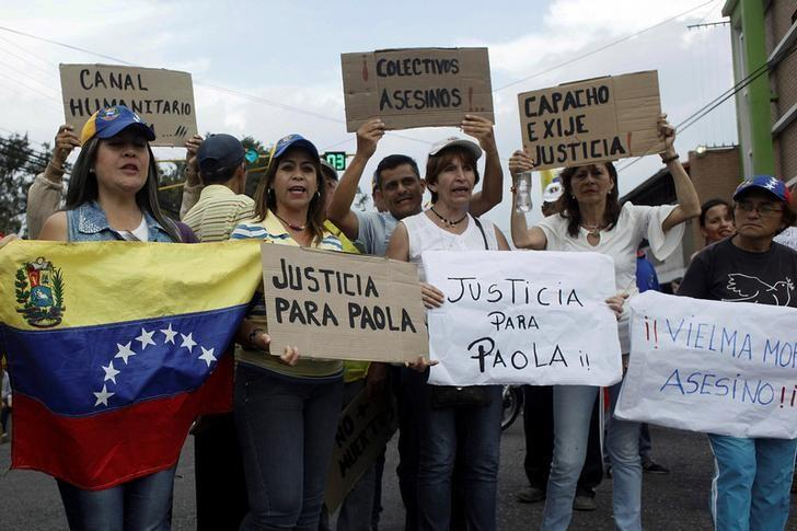 People holding placards gather outside the wake of Paola Ramirez, a student who died during a protest, in San Cristobal, Venezuela April 20, 2017. REUTERS/Carlos Eduardo Ramirez