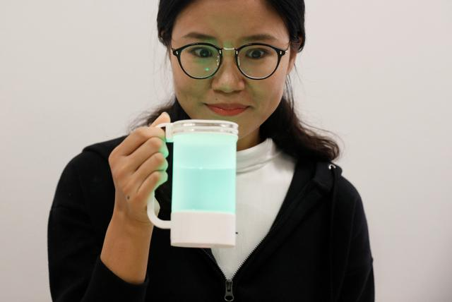 An NUS student tastes a virtual lemonade simulator, which uses electrodes to mimic the flavour and LED lights to imitate the color of real lemonade, at the National University of Singapore campus in Singapore April 13, 2017. REUTERS/Edgar Su