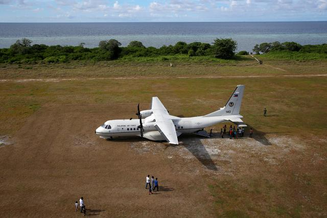 People walk towards a parked Philippine Air Force plane in Philippine occupied Thitu Island in the Spratly Islands in the disputed South China Sea, April 21, 2017. REUTERS/Erik De Castro