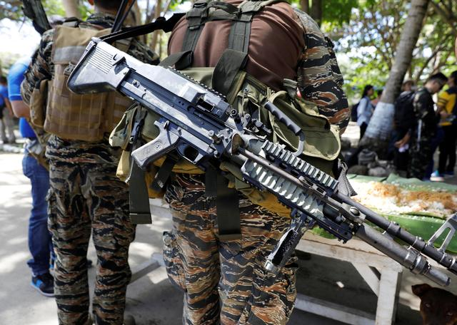 An assault weapon is pictured while a Filipino soldier eats a meal in Philippine occupied Thitu Island on Spratly Islands in disputed South China Sea, April 21, 2017. REUTERS/Erik De Castro