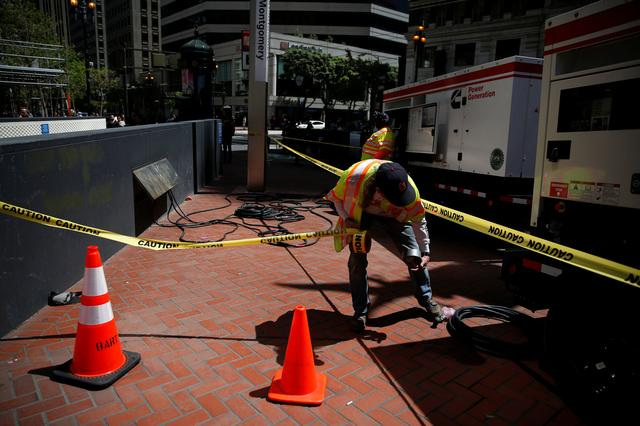 A Bay Area Rapid Transit (BART) worker pulls a caution tape near two generators above Montgomery station during a major power outage in San Francisco, California, U.S., April 21, 2017. REUTERS/Stephen Lam