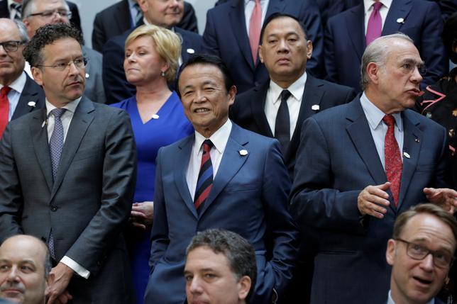 4月21日、麻生太郎財務相(写真中央)は20カ国・地域(G20)財務相・中央銀行総裁会議後にワシントンで記者会見し、「これ以上自由貿易から保護主義への流れがさらに強まるとは思っていない」との認識を示した。中国経済については「過剰生産や過剰投資が世界経済に混乱を与えている」と懸念を表明した。写真はG20での集合写真(2017年 ロイター/Yuri Gripas)