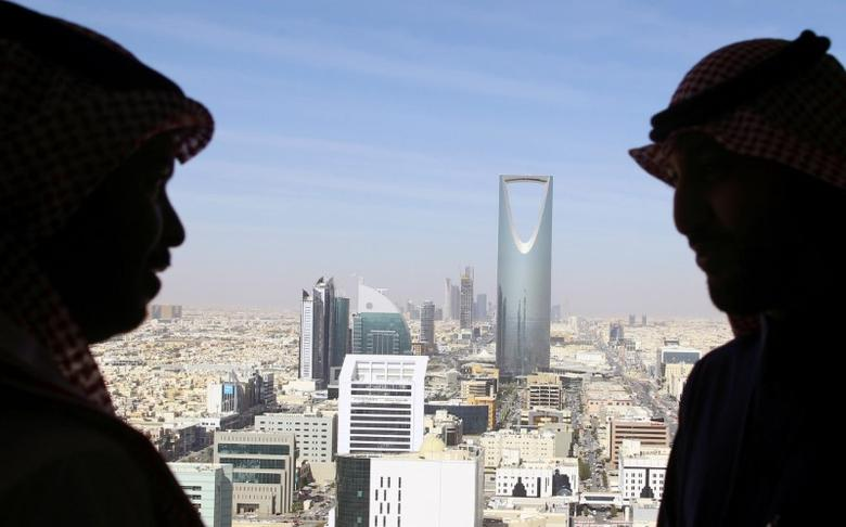 FILE PHOTO: Men look out of a building as the Kingdom Centre Tower is seen in Riyadh, Saudi Arabia, January 1, 2017.   REUTERS/Faisal Al Nasser/File Photo