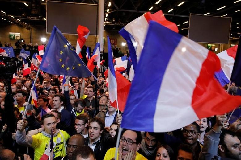 Supporters of Emmanuel Macron, head of the political movement En Marche !, or Onwards !, and candidate for the 2017 French presidential election, celebrate after partial results in the first round of 2017 French presidential election, at the Parc des Expositions hall in Paris, France April 23, 2017.   REUTERS/Philippe Wojazer