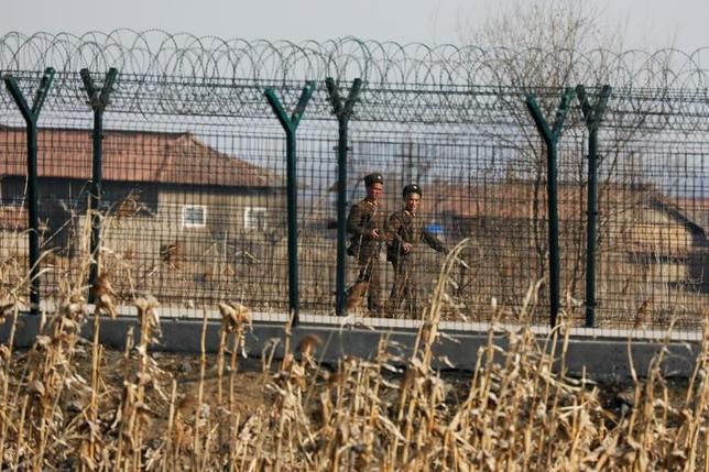 4月24日、国際人権団体「ヒューマン・ライツ・ウォッチ(HRW)」は、北朝鮮を脱出し中国で先月身柄を拘束された8人について、北朝鮮に強制送還される可能性があると明らかにした。写真は中国国境のフェンス沿いに警備する北朝鮮兵士。3月撮影(2017年 ロイター/Damir Saglj)