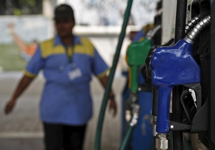 An employee stands next to a fuel pump at a fuel station in New Delhi, India, March 7, 2016. REUTERS/Adnan Abidi/Files