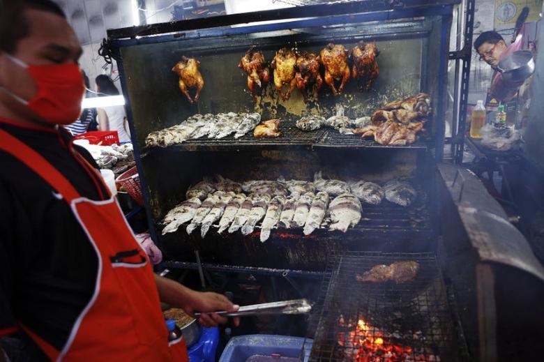 Men work at a street food restaurant in central Bangkok March 2, 2013.  REUTERS/Damir Sagolj