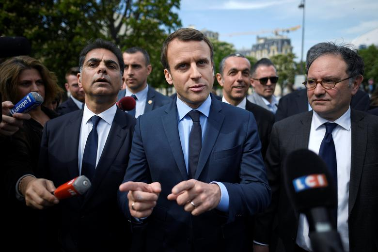 Emmanuel Macron (C), head of the political movement En Marche !, or Onwards !, and candidate for the 2017 French presidential election, next to Mourad Franck Papazian (L), co-president of France's Armenian Organizations Coordination Council (CCAF, Conseil de Coordination des organisations Armenienne de France), speaks to the press after a ceremony at a monument in memory of mass killings of Armenians by Ottoman forces in 1915, in Paris, France, April 24, 2017 . REUTERS/Lionel Bonaventure/Pool