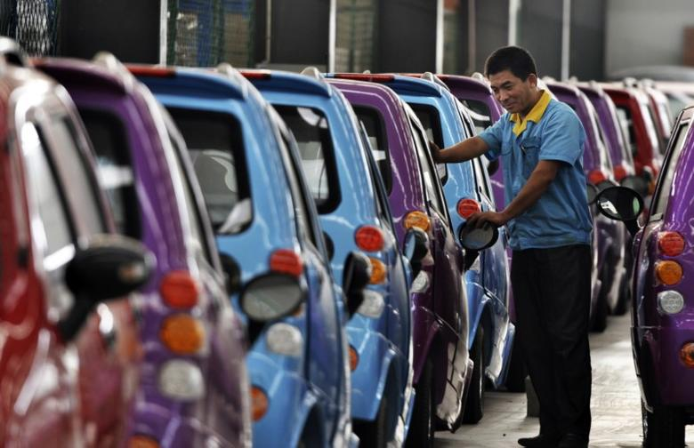 An employee checks newly-assembled electric cars to be exported to South America at an electric vehicle factory in Zouping county, Shandong province September 24, 2013. REUTERS/China Daily