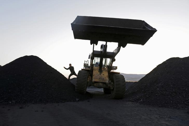 FILE PHOTO: A driver gets off a loading vehicle at local businessman Sun Meng's small coal depot near a coal mine of the state-owned Longmay Group on the outskirts of Jixi, in Heilongjiang province, China, October 23, 2015.  REUTERS/Jason Lee/File Photo