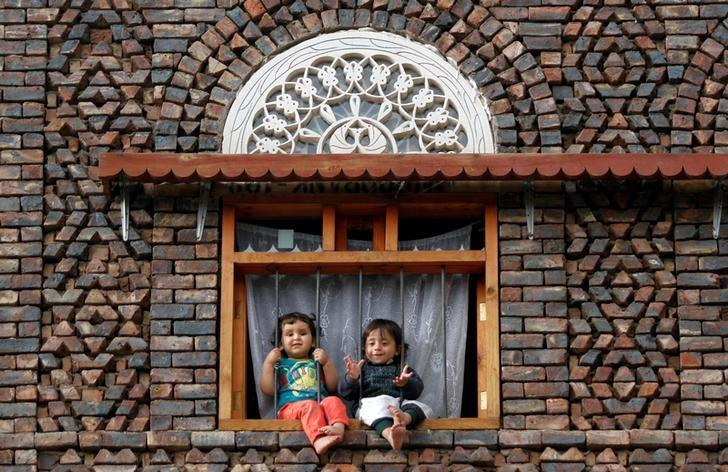 Children sit in a window as they look at supporters of the Houthi movement who attend a pro-Houthi rally in Sanaa, Yemen February 17, 2017. REUTERS/Mohamed al-Sayaghi/Files