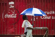 A woman walks by a store decorated with a Coca-Cola logo in the town of Ahero near Kisumu, Kenya April 20, 2017. REUTERS/Baz Ratner - RTS136QS