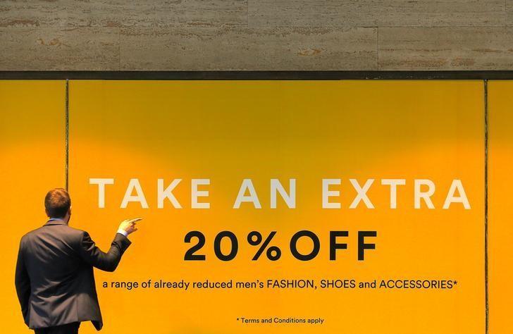 2017年4月12日,澳洲悉尼,一名男子站在商店的促销广告前。REUTERS/Steven Saphore