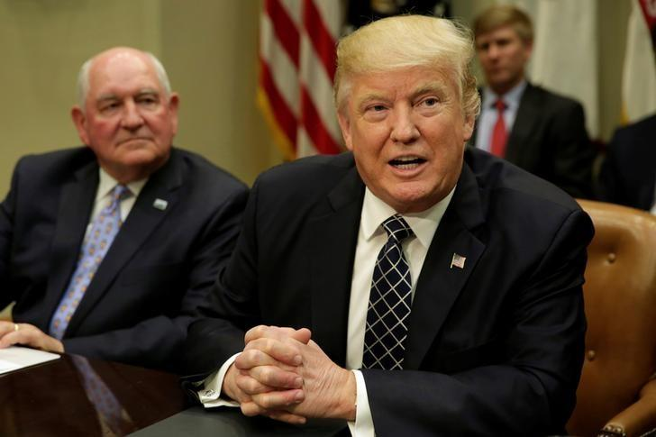 U.S. President Donald Trump talks to the media next to Secretary of Agriculture Sonny Perdue during a roundtable discussion with farmers at the White House in Washington, U.S. April 25, 2017. REUTERS/Yuri Gripas