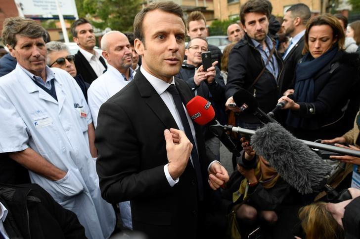 Emmanuel Macron (C), head of the political movement En Marche !, or Onwards !, and candidate for the 2017 French presidential election, speaks to journalists during a visit to the Hopital Raymond-Poincare in Garches, near Paris, France, April 25, 2017.   REUTERS/Lionel Bonaventure/Pool