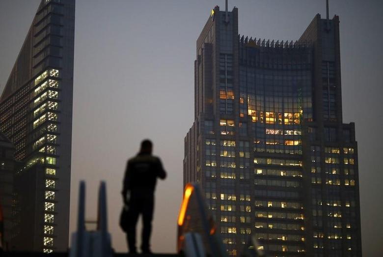 资料图片:2013年11月,上海浦东陆家嘴金融区,一名男子站在一部扶梯上。REUTERS/Carlos Barria