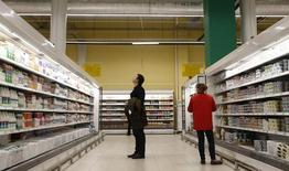 An employee and a visitor stand next to shelves stocked with dairy products at a grocery store which is the 100th store of French retail group Auchan opened in the country, in Moscow, Russia, December 13, 2016.  REUTERS/Maxim Shemetov