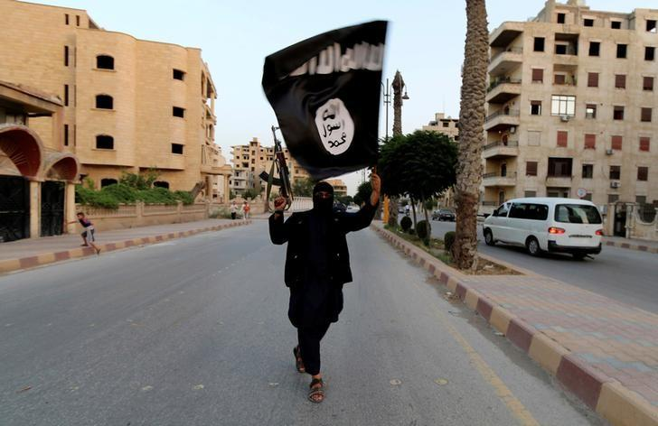 A member loyal to the Islamic State in Iraq and the Levant (ISIL) waves an ISIL flag in Raqqa June 29, 2014. REUTERS/Stringer/File Photo