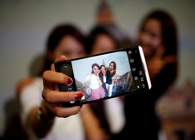 FILE PHOTO: Models pose for photographs with a LG electronics' new V20 premium smartphone during its unveiling ceremony in Seoul, South Korea, September 7, 2016.  REUTERS/Kim Hong-Ji/File Photo