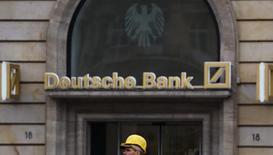 Deutsche Bank informó de un salto de un 143 por ciento en el beneficio neto del primer trimestre a 575 millones de euros, gracias a unos menores costes por sus problemas legales del pasado y un rebote en la negociación de deuda. En la imagen, un obrero de la construcción bajo un cartel de la entidad en Fráncfort el 27 de octubre de 2016.   REUTERS/Kai Pfaffenbach