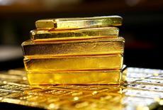 Золотые слитки. Цена на золото снизилась в четверг на спаде глобального аппетита к риску, однако скептицизм вокруг нового плана налоговых реформ,представленного президентом США Дональдом Трампом, сдержал дальнейшее падение.   REUTERS/Leonhard Foeger/File Photo