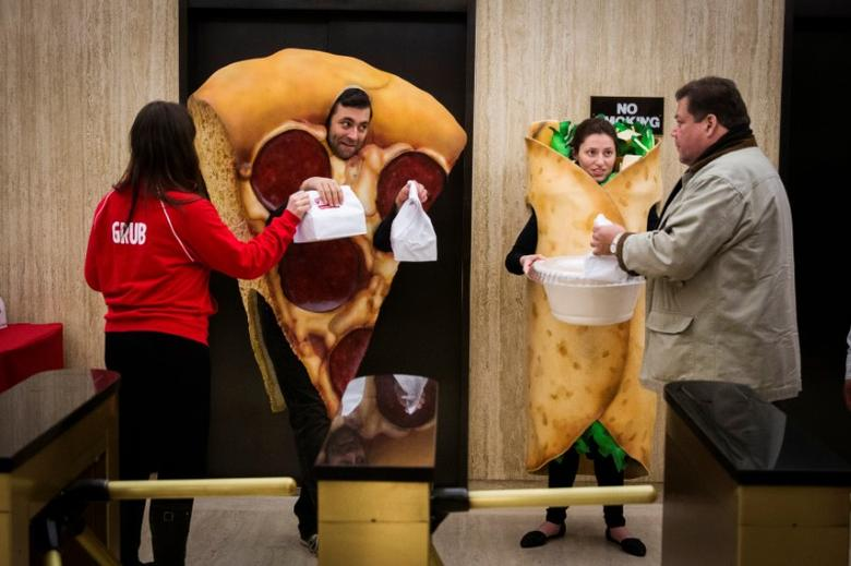 FILE PHOTO: People dressed in food-themed costumes give away donuts to people headed to the floor of the New York Stock Exchange to celebrate the IPO of GrubHub, in New York April 4, 2014.  REUTERS/Lucas Jackson/File Photo