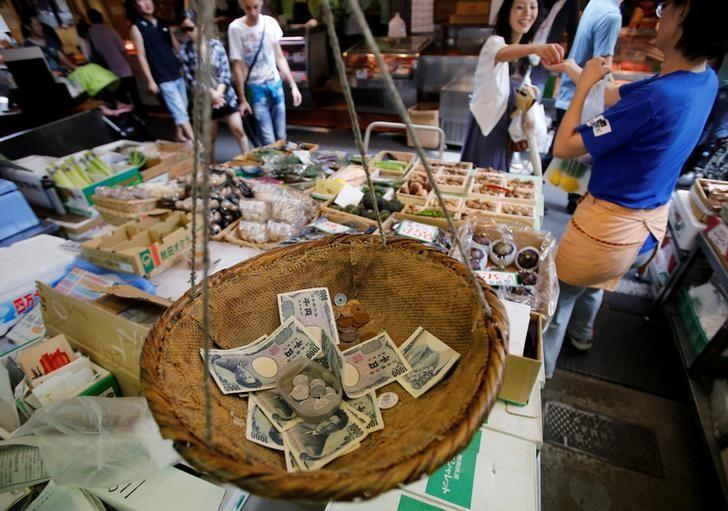 Coins and banknotes that are used for change are seen in a bamboo basket at a greengrocer in Tokyo August 22, 2013. REUTERS/Toru Hanai/Files