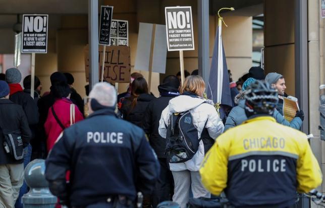 4月27日、トランプ米大統領が署名した大統領令で入国制限の対象となった7カ国の国民向けに3月に発給された一時ビザの数は、前年度平均を約40%下回った。米政府の暫定データをロイターが分析した。写真は入国制限に関して抗議をする人々。シカゴで3月撮影(2017年 ロイター/Kamil Krzaczynski)