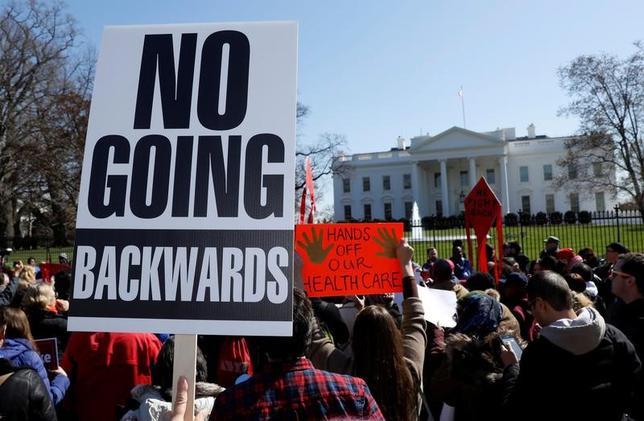 4月27日、米下院指導部は、修正を加えた医療保険制度改革(オバマケア)改廃法案に対する十分な支持が集まっていないため、同案の採決を今週中には実施しないことを決めた。写真は米議会議事堂の外でオバマケア廃止に抗議する市民ら。3月撮影(2017年 ロイター/Kevin Lamarque)
