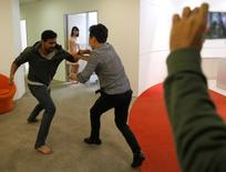 "Graymatics employees pretend to fight as they record footage to be used to ""train"" their software to watch and filter internet videos for violence, at their office in Singapore April 27, 2017.  REUTERS/Edgar Su"