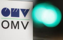 The logo of Austrian oil and gas company OMV is pictured behind traffic lights at its headquarters in Vienna September 12, 2014. Russian gas deliveries to Austria were down up to 15 percent on Friday but within a range of fluctuation normal for the season, a spokesman for OMV said.  REUTERS/Heinz-Peter Bader (AUSTRIA - Tags: BUSINESS LOGO POLITICS ENERGY)
