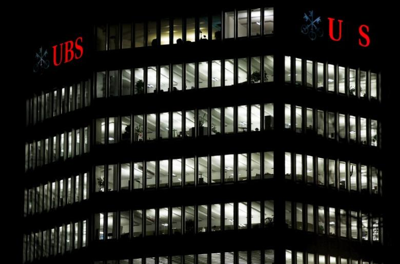 A partially illuminated (R) and a fully illuminated logo of Swiss bank UBS are seen on a building in Zurich December 18, 2012.  REUTERS/Michael Buholzer/File Photo