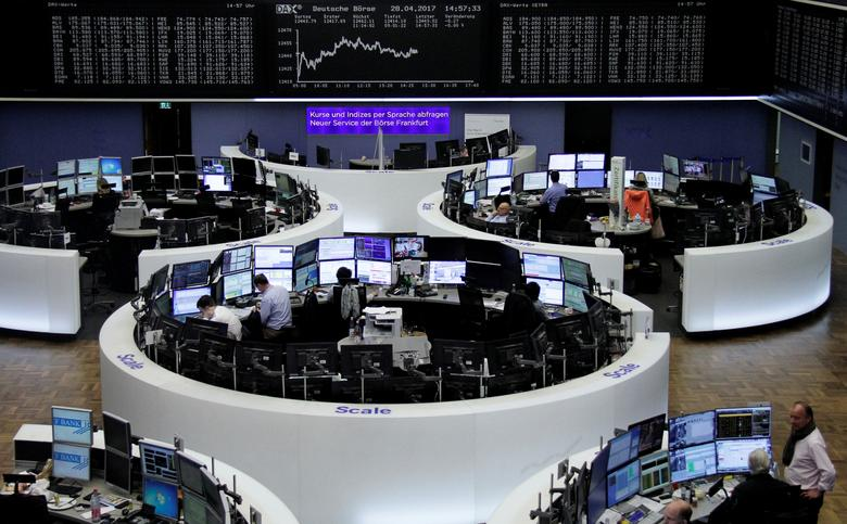 Traders work at their desks in front of the German share price index, DAX board, at the stock exchange in Frankfurt, Germany, April 28, 2017. REUTERS/Staff/Remote