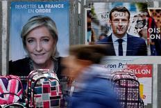 El Ibex-35 cerró la semana más positiva desde la primera de marzo al alejarse la posibilidad de un triunfo electoral del populismo de derechas en Francia, mientras el mercado se mantiene pendiente de las políticas de Donald Trump en EEUU. En la imagen, una mujer pasa por delante de carteles electorales de Marine Le Pen y Emmanuel Macron en un mercado de la localidad francesa de Bethune, el 24 de abril de 2017. REUTERS/Pascal Rossignol