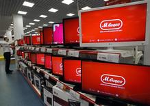 A sales assistant arranges televisions on display in a M. Video shop in St.Petersburg, March 27, 2013. Russian home electronics retailer M.Video reported on Wednesday a 23 percent rise in 2012 net profit thanks to higher sales.  REUTERS/Alexander Demianchuk (RUSSIA - Tags: BUSINESS)