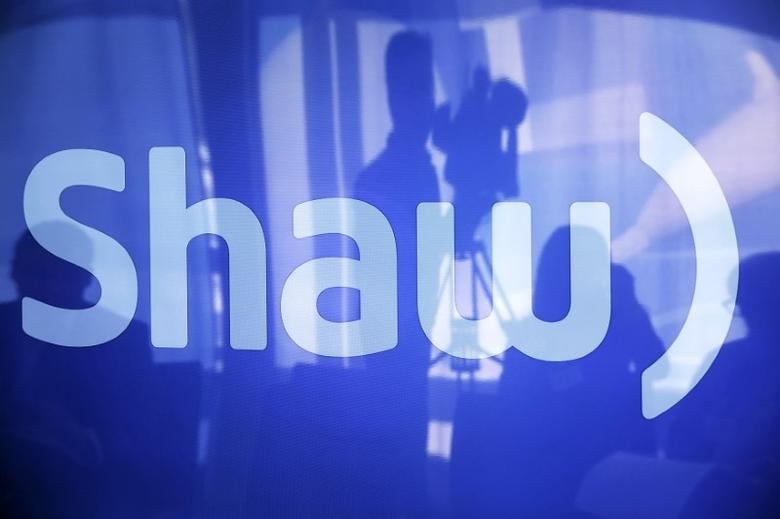 A television cameraman is reflected on a television screen displaying the Shaw logo during the Shaw AGM in Calgary, Alberta, January 14, 2014. REUTERS/Todd Korol