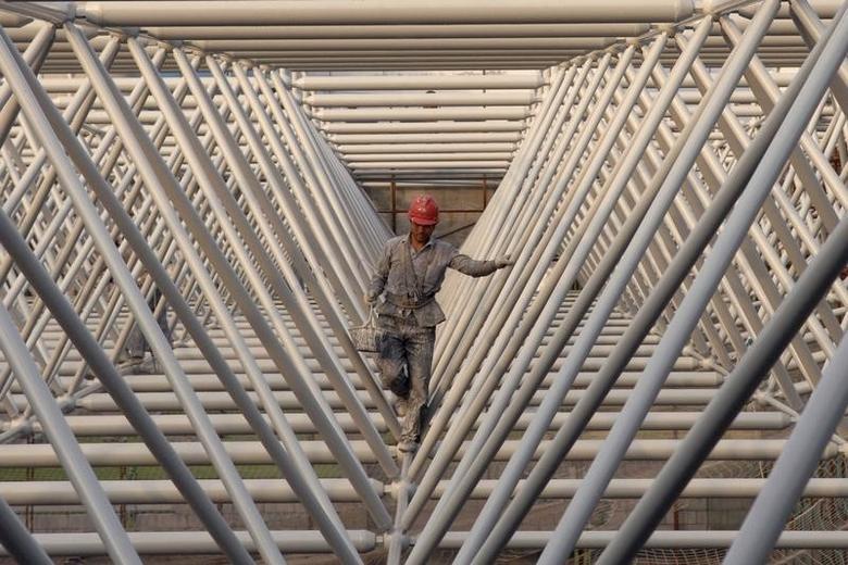 资料图片:2007年6月,江苏淮安一处建筑工地的工人穿过钢结构物。REUTERS/Patty Chen