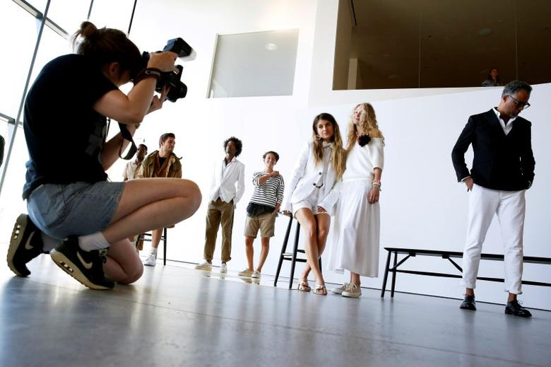 A woman takes a photograph as models pose during a presentation of the J. Crew Spring/Summer 2017 collection during New York Fashion Week in the Manhattan borough of New York, U.S., September 11, 2016.  REUTERS/Lucas Jackson
