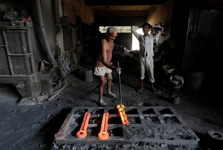 A worker makes parts for lamp posts inside an iron casting factory in Ahmedabad, India March 1, 2017. REUTERS/Amit Dave