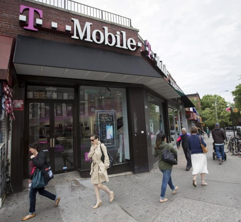 FILE PHOTO: People pass by a T-Mobile store in the Brooklyn borough of New York June 4, 2015. REUTERS/Brendan McDermid
