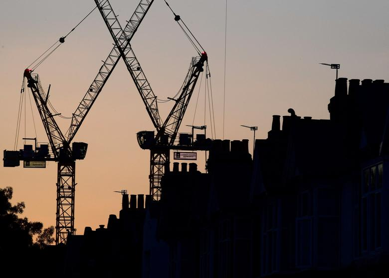 FILE PHOTO: Construction cranes are seen on a residential building project behind homes in London, Britain, October 26, 2016.   REUTERS/Toby Melville/Files