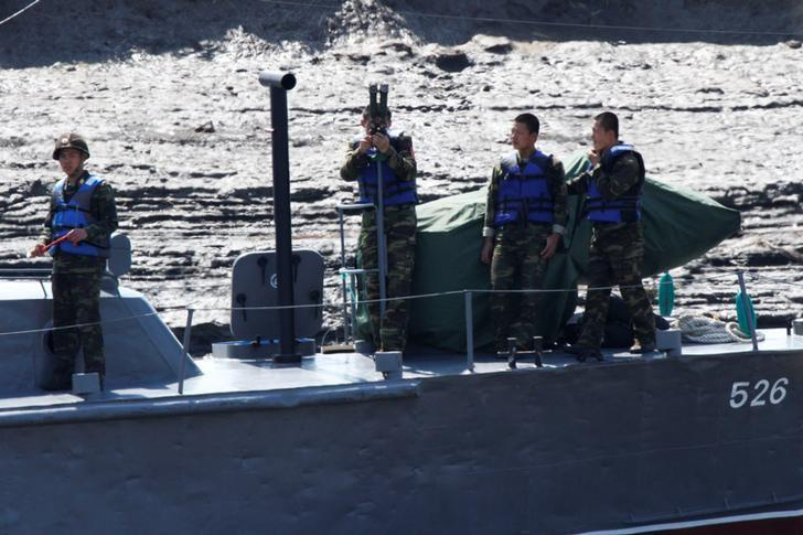 North Korean soldiers observe from a vessel on the Yalu river, near the Chinese border city of Dandong, May 2, 2017. Picture taken May 2, 2017. Picture taken from the Chinese side of the Yalu River. REUTERS/Jacky Chen