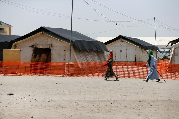 A man and a woman walk past the World Food Programme (WFP) tents at the Banki IDP camp, Borno, Nigeria April 27, 2017. Picture taken April 27, 2017. REUTERS/Afolabi Sotunde