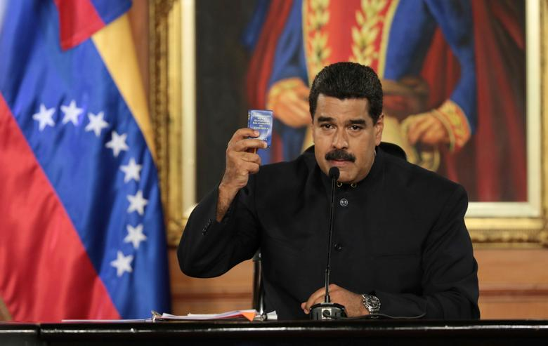 Venezuela's President Nicolas Maduro holds a copy of the Venezuelan constitution as he speaks during a ceremony at Miraflores Palace in Caracas, Venezuela May 1, 2017. Miraflores Palace/Handout via REUTERS