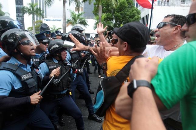 5月3日、財政危機に陥っていた米自治領プエルトリコは、公的債務の再編を行うことを明らかにした。規模3兆8000億ドルの米地方債市場で過去最悪の破綻となる可能性がある。写真は警察と衝突する財政緊縮策に抗議する市民ら。1日撮影(2017年 ロイター/Alvin Baez)