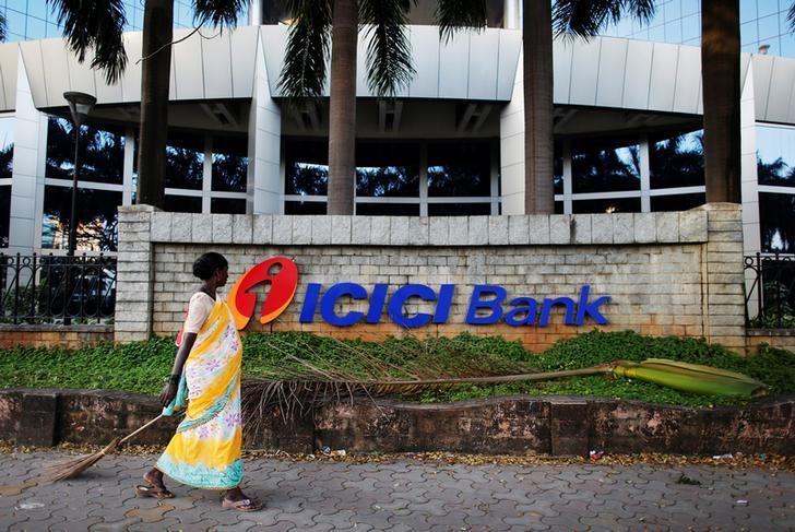 FILE PHOTO: A municipal worker walks past a logo of ICICI Bank at its headquarters in Mumbai October 25, 2013.  REUTERS/Danish Siddiqui/File Photo
