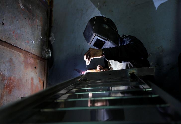 A worker welds steel pipes to make a counter at a steel furniture manufacturing unit in Ahmedabad, India September 1, 2016. REUTERS/Amit Dave/Files